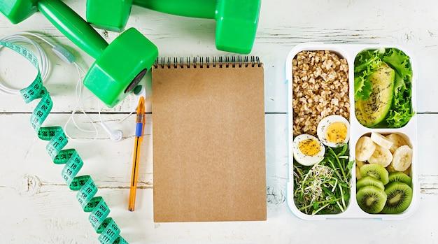 Lunchbox met gekookte eieren, havermout, avocado, microgroenten en fruit.
