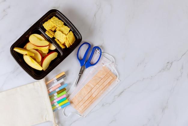 Lunchbox met gesneden appel, crackers en schoolspullen
