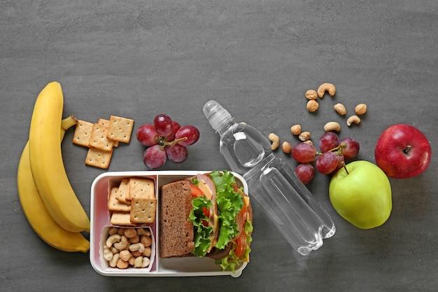 Lunchbox met sandwich en verschillende producten op donkere achtergrond