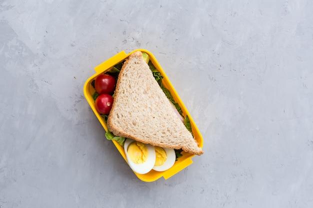 Lunchbox met sandwich en verschillende producten op grijs