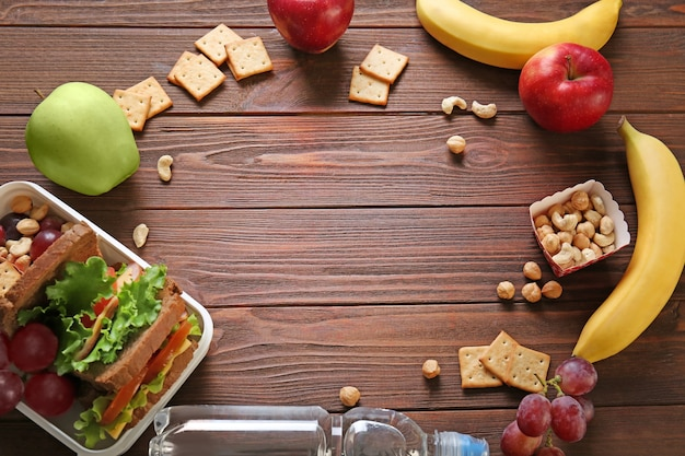 Lunchbox met sandwich en verschillende producten op houten ondergrond