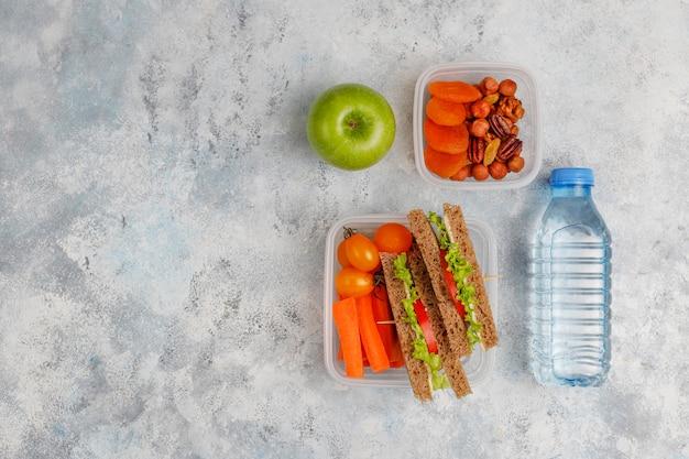 Lunchbox met sandwich, groenten, fruit op wit.
