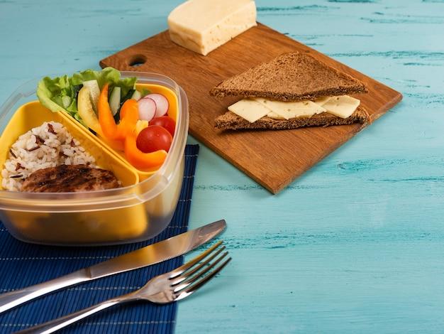 Lunchbox met smakelijk eten en op lichte houten tafel.