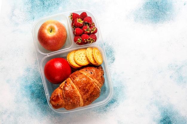 Lunchbox met vers gebakken croissant, crackers, fruit en frambozen.