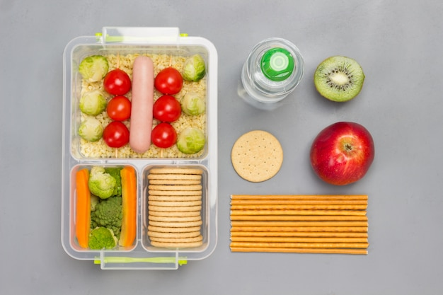 Lunchbox met worst, broccoli en tomaten.