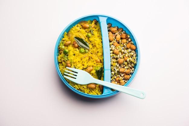 Lunchbox of tiffin voor indiase kinderen, hete poha gemaakt van geklopte rijst en kruiden, vergezeld van spruitjes