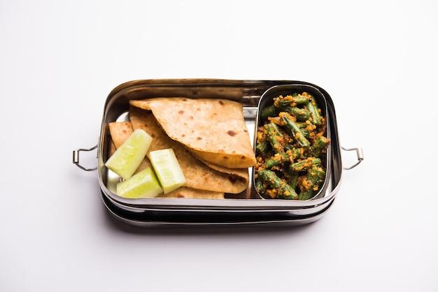 Lunchbox of tiffin voor indiase kinderen, inclusief bonen, plantaardige sabzi met roti of chapati, selectieve focus