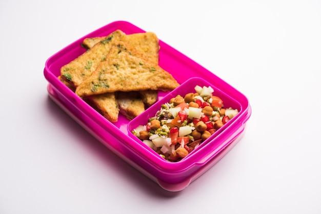 Lunchbox of tiffin voor indiase kinderen, inclusief brood omelet pakora met tomatenketchup of spruitjes, selectieve focus