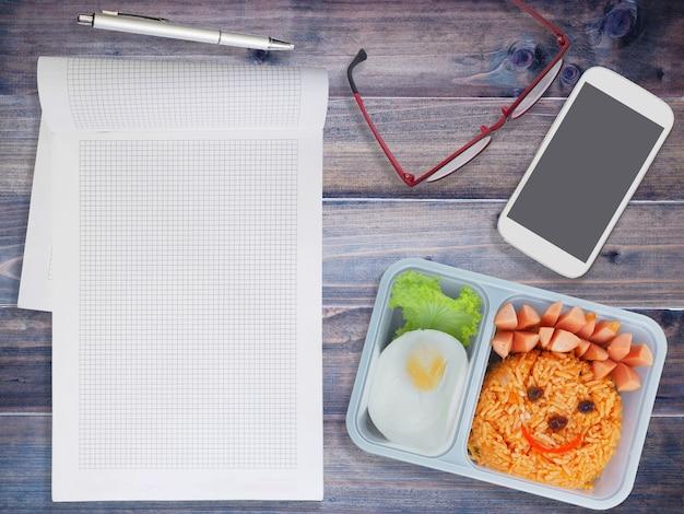 Lunchbox voor kinderen met mobiele telefoon en notitieblok op houten achtergrond. terug naar school-concept.