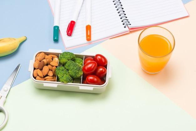 Lunchbox voor school, rijst verpakt in zeewier met worst, ei en appel. bovenaanzicht.