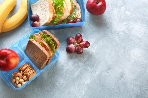 Lunchboxen met sandwiches en verschillende producten op grijze achtergrond