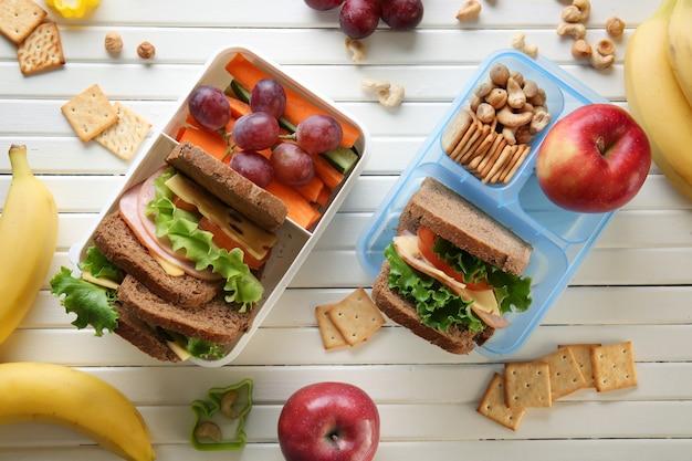 Lunchboxen met sandwiches en verschillende producten op houten ondergrond