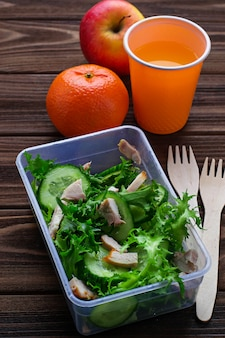 Lunchdoos met salade, appel, mandarijn en sap.