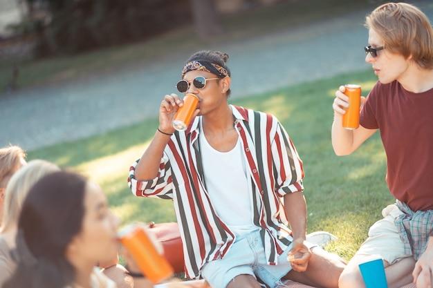 Lunchen met vrienden. twee gelukkige jongens met een zonnebril die eten en drinken op een avondpicknick met hun groepsgenoten.