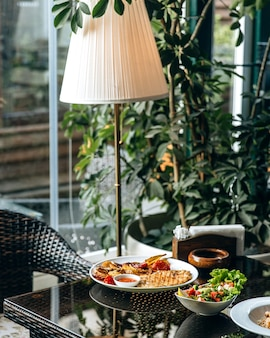 Lunchopstelling in het restaurant bij het raam en de staande lamp