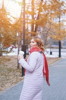 Lunchpauze. een meisje eet een taart en drinkt koffie in het park op een bankje. voedsellevering. het verlangen om op te warmen op een herfstdag