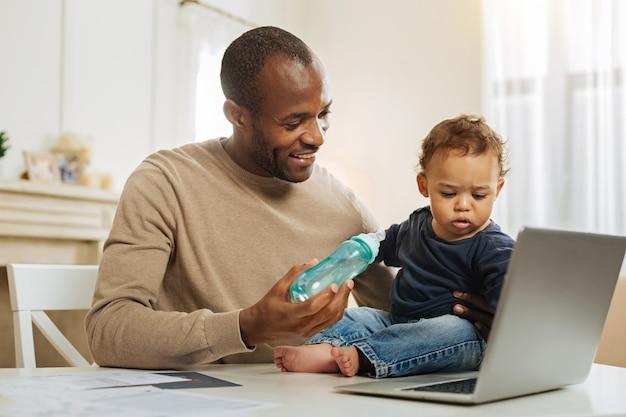 Lunchtijd. aantrekkelijke vrolijke bebaarde afro-amerikaanse man die lacht en zijn kind voedt terwijl hij achter de laptop zit