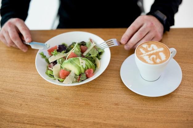 Lunchtijd! mannelijke werknemer die zijn heerlijke en gezonde maaltijd eet. man genieten van salade en plat wit. zorg goed voor jezelf en vergeet niet te eten voor het werk. gesneden weergave van mannelijke handen met mes en vork.