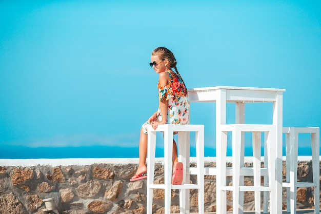 Lunchtijd meisje ontbijten op terras met uitzicht op zee