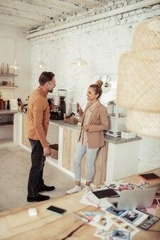 Lunchtijd. twee lachende collega's praten en drinken samen koffie in de keuken.