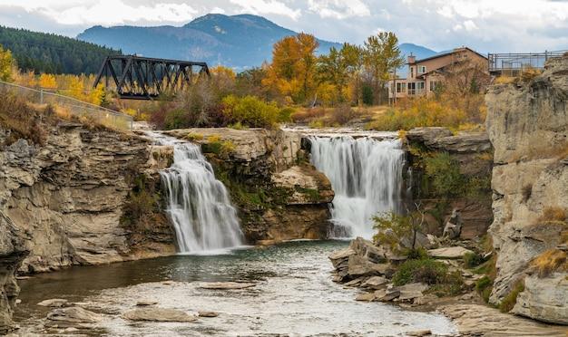 Lundbreck falls, een waterval van de crowsnest river in het gebladerteseizoen van de herfst. een ijzeren brug voor spoorrails op de achtergrond. alberta, canada.
