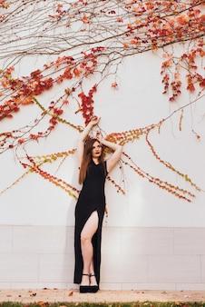 Luxe aantrekkelijke jonge vrouw in zwarte jurk poseren tegen muur in de open lucht