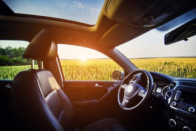Luxe auto binnen interieur. stuurwiel, versnellingspook, lederen salon, dashboard en panoramadak. crossover suv op het platteland met zonsondergang op de achtergrond.