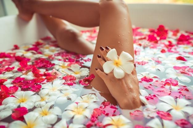 Luxe badkuip in spa met blote benen van de vrouw zien door.