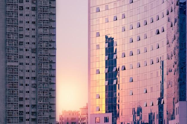 Luxe bedrijfsgebouw bij zonsondergang, grijs armoedig woongebouw.