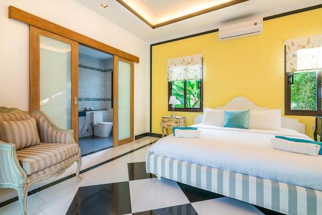 Luxe binnenhuisarchitectuur in slaapkamer van poolvilla met hoog opgeheven plafond en rozen op bed in het huis of het huisgebouw