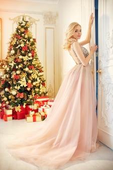 Luxe blonde in een avondjurk in de buurt van een kerstboom