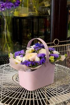 Luxe boeket met een delicate lichtroze ranonkel in een modieus roze doosje in de vorm van een tas of mand.