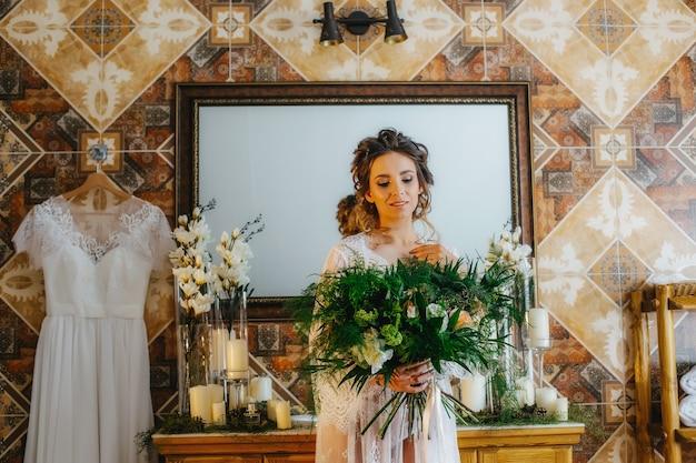 Luxe bruid in een prachtig kanten gewaad met een boeket bloemen en groen