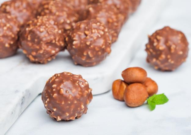 Luxe chocoladesuikergoed met stukjes hazelnoot en muntblad op marmeren tafel.