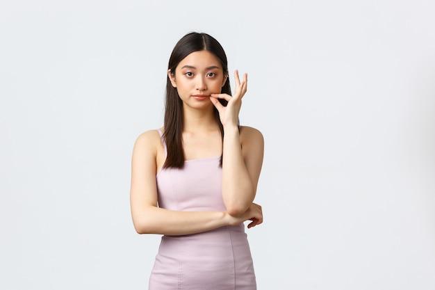 Luxe concept voor vrouwen, feesten en vakanties. serieus ogende schattig aziatisch meisje in een elegante jurk