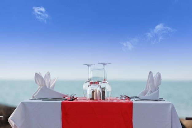 Luxe eettafel op strand in blauwe lucht
