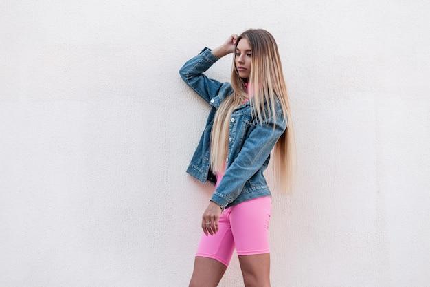 Luxe europese jonge vrouw in een modieuze denim jurk in stijlvolle roze korte broek met mooi lang blond haar vormt buiten in de buurt van een vintage gebouw. glamoureuze meid geniet van een wandeling op een zomerse dag.