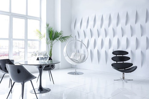 Luxe futuristisch trendy modern interieur in contrasterende zwart-witte kleuren met interessante modieuze zwarte meubels en gedecoreerde muur