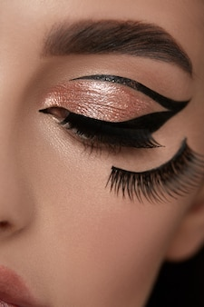 Luxe gouden mua met zwarte eyeliner en wimpers onder het oog