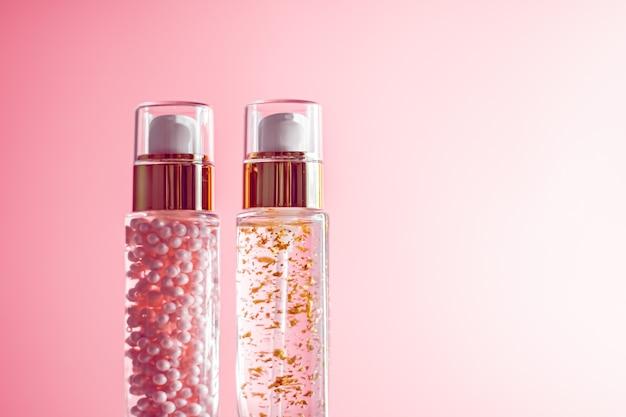 Luxe huidverzorgingsproducten in glazen flessen op roze achtergrond
