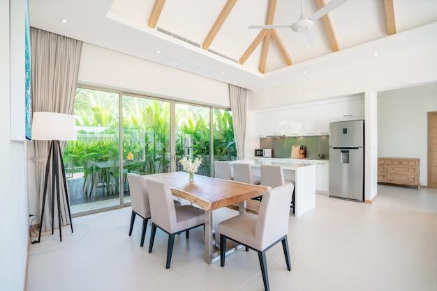 Luxe interieur in de woonkamer van villa's met zwembad. luchtige en lichte ruimte met hoog verhoogd plafond met open keuken
