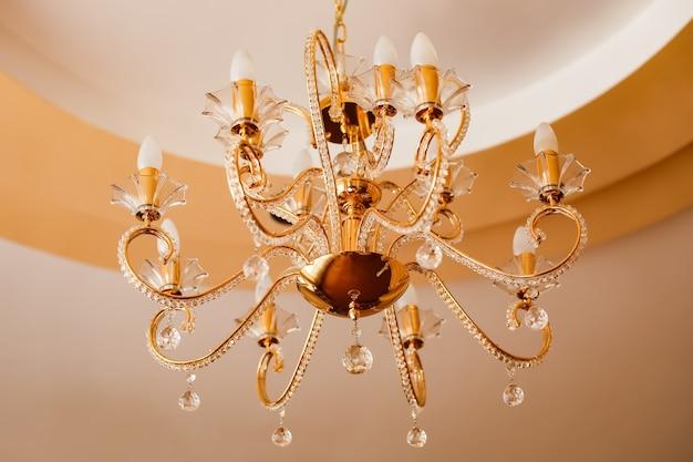 Luxe interieur kroonluchter met kaarsen. aan het plafond hangt een nobele kandelaar met veel kleine pareltjes.