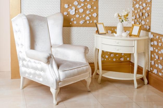 Luxe interieur. luxe witte fauteuil, antiek gebeeldhouwde meubels, klassiek interieur detail.