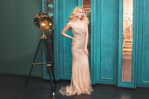 Luxe jonge mooie model blonde vrouw in een chique lange gouden jurk in het interieur