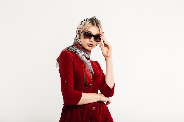 Luxe jonge vrouw mannequin rechtzetten zonnebril binnenshuis. sexy blonde meisje met modieuze luipaard sjaal op hoofd met mooie lippen in stijlvolle bordeauxrode jurk poseren. retro stijl.