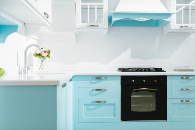 Luxe keukeninterieur in witte en blauwe tinten, niemand. modern huismeubilair, spoelbak met kraan, afzuigkap, ingebouwd fornuis en oven, ontwerp van kookplaats
