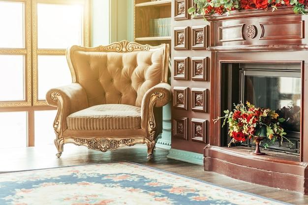 Luxe klassiek interieur van huisbibliotheek zitkamer met boekenplank, boeken, fauteuil, bank en open haard