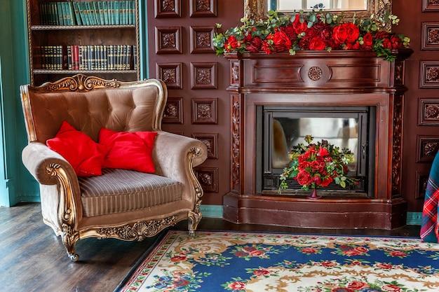 Luxe klassiek interieur van thuisbibliotheek. zitkamer met boekenplank, boeken, fauteuil, bank en open haard.