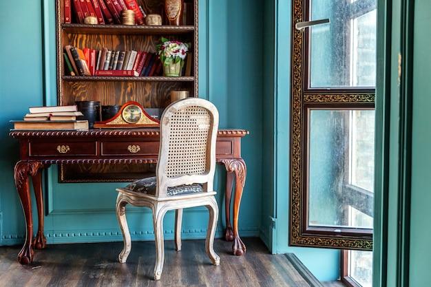 Luxe klassiek interieur van thuisbibliotheek. zitkamer met boekenplank, boeken, tafel en stoel.