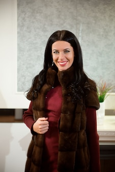 Luxe kledingconcept. vrouw met bontjas. meisje in een bontjasjas in winkel met bont op achtergrond.